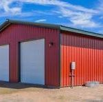 Large Barn in corrugated metal with two large white doors. Walls of barn are painted a dark red