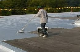 Man on roof applying silver coloure bitumen aluminium paint with a roller