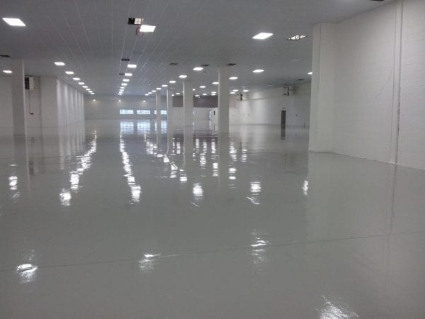 Brightly lit indoor car park with shiny floor painted with Carbotread