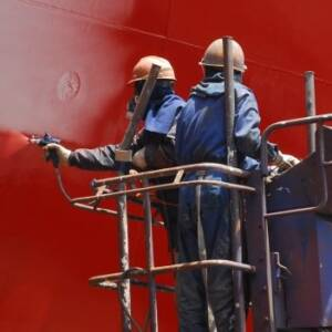 Two workers spraying red fast dry gloss paint