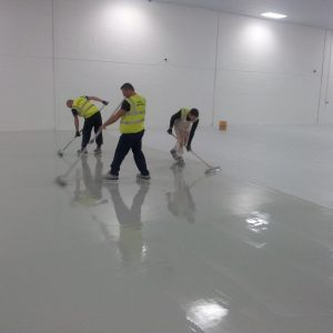 Workers painting an internal warehouse floor leaving it bright and shiny