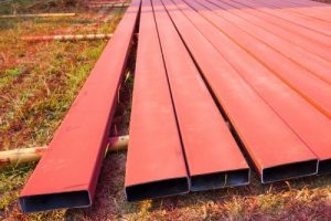 nine steel box sections in a matt red finish having been coated with red oxide primer