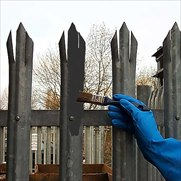 A gloved hand brush painting primer onto galvanised metal railings