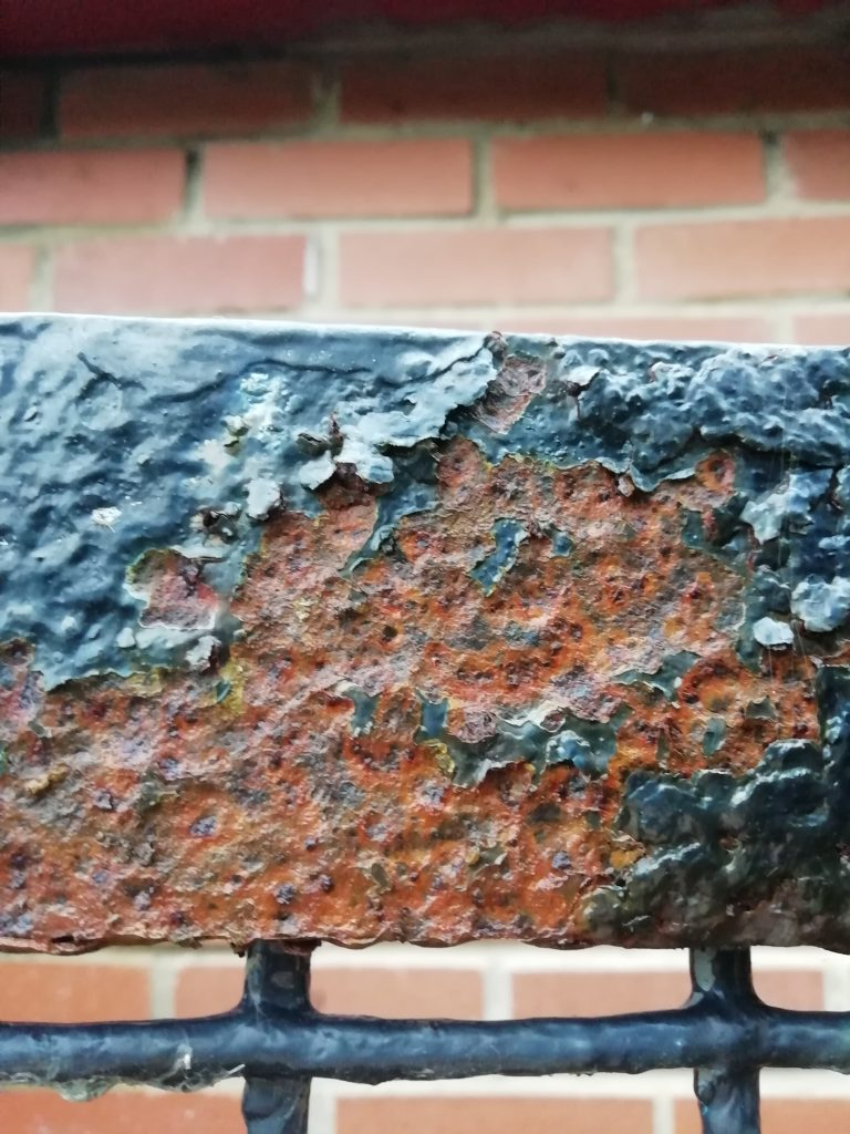 Close up of red brown rust formation on top bar of metal gate
