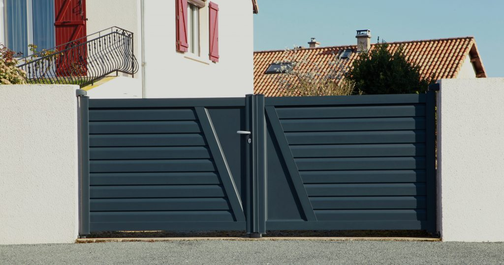 Set of large wooden gates adjacent to white painted property. Gates are painted dark grey in a satin finish