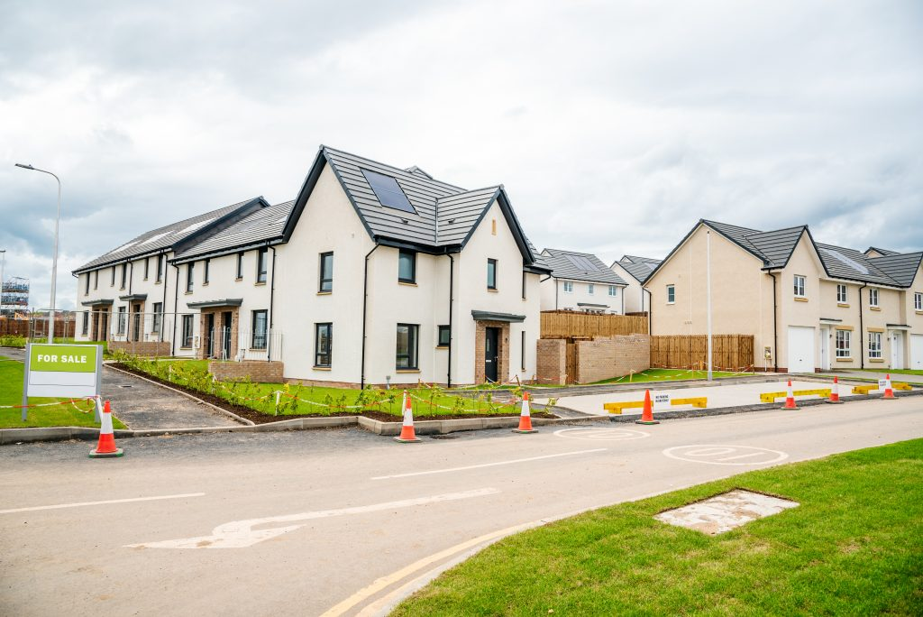New build houses on road junction. Houses are painted white with dark grey window frames and guttering