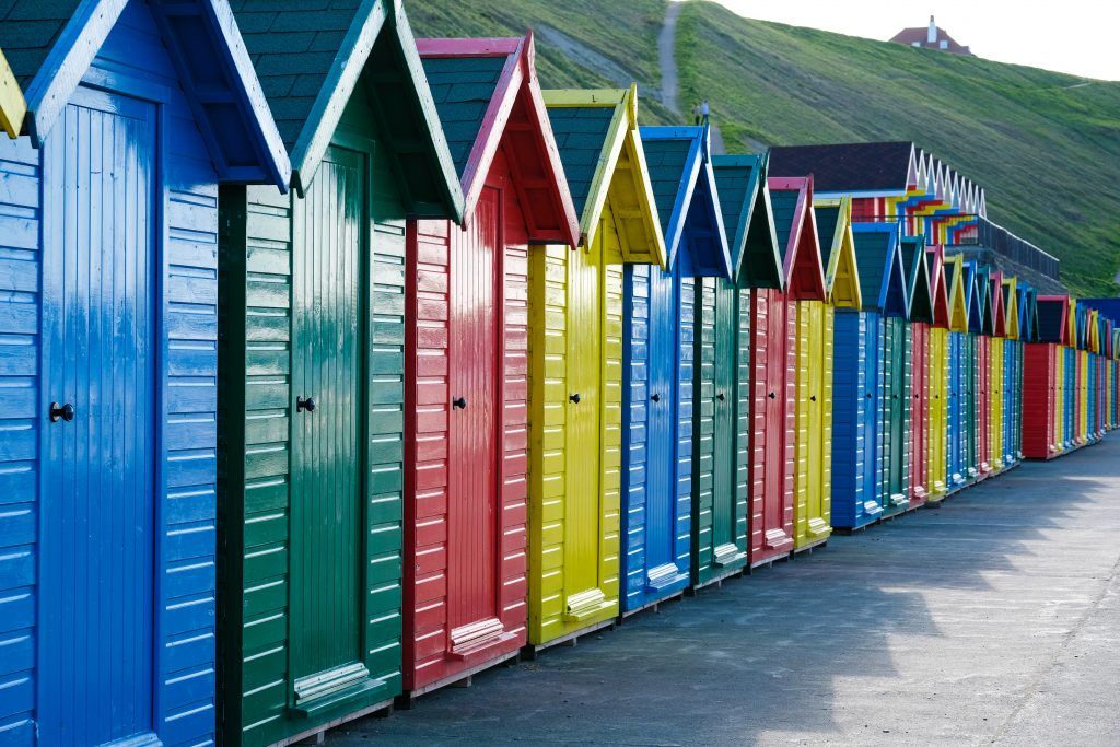 Row of beach huts in bright primary colours to illustrate the use of protective topcoat paint