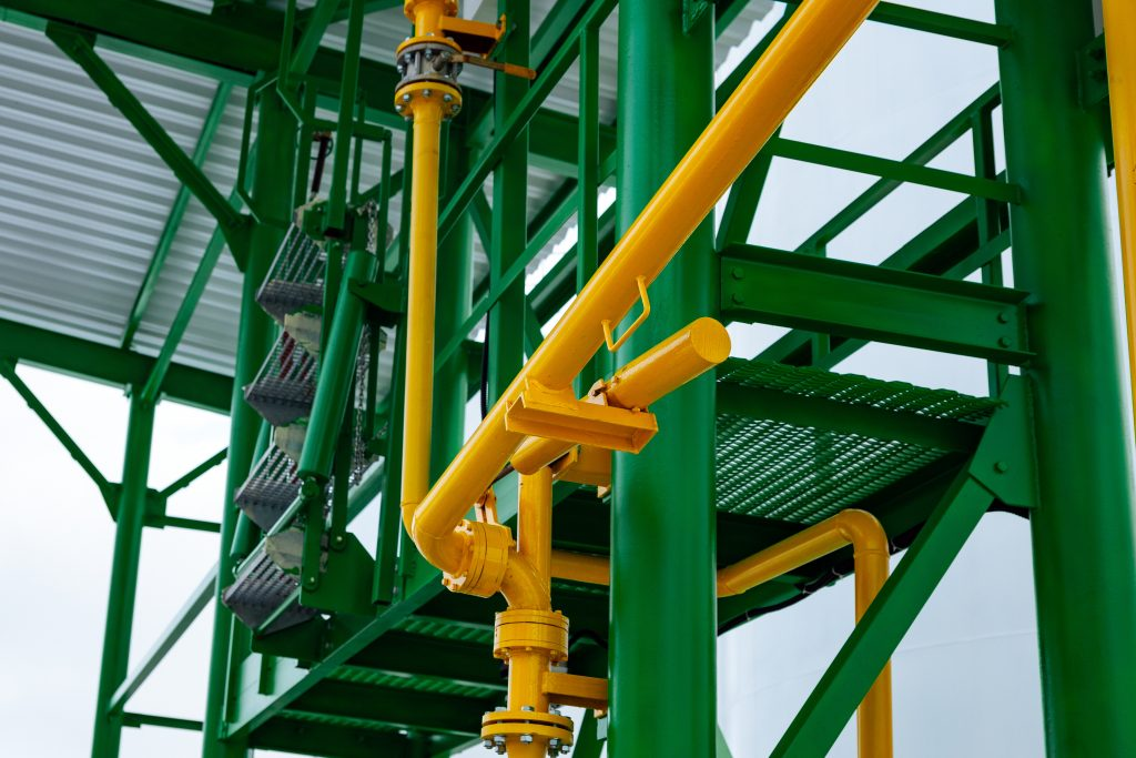 Metal industrial walkway and pipework painted in gloss green and yellow paint to illustrate the use of protective paint topcoat.