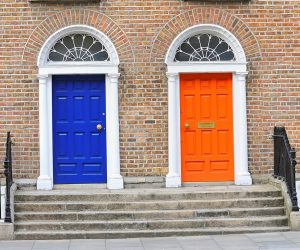 Two brightly painted neighbouring Georgian doors in brick building one is bright blue and the other orange. Steps lead up to both