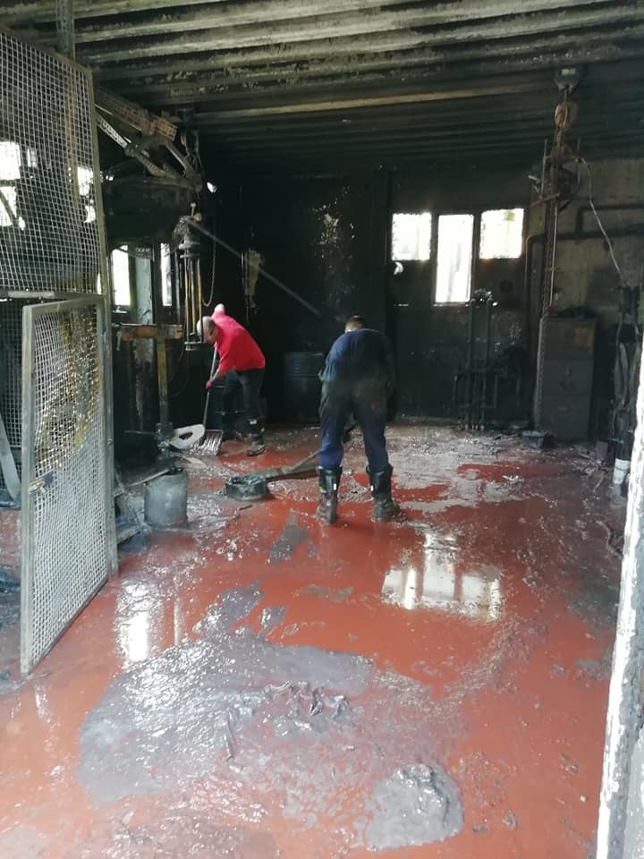 Workmen cleaning up in burnt out factory room
