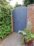 Grey painted gate in red brick wall with green planting