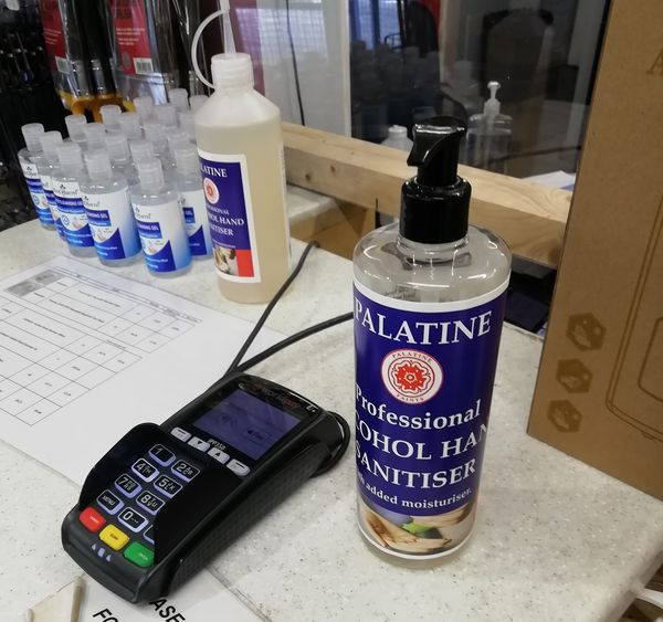 Paint trade counter with card machine, clear screens and sanitiser