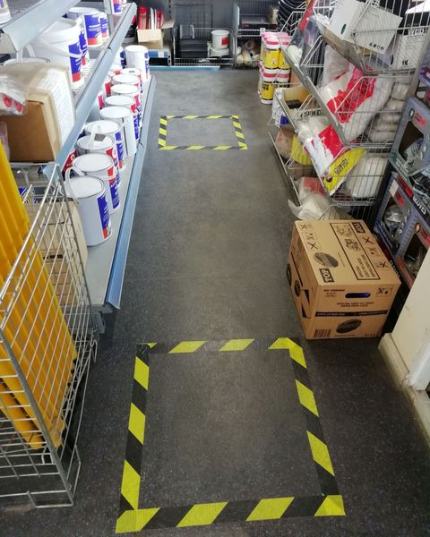 aisle in paint trade shop with safe distancing space marked with yellow and black hazard floor tape