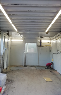 Decorator painting wall of brightly lit warehouse white