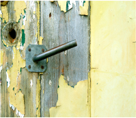Wooden door with faded yellow paint flaking off